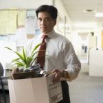Fired Chinese businessman carrying box of personal items