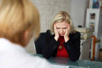 Depressed blonde senior employee dismissed in office